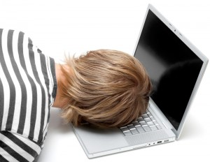 Person with head on computer keyboard